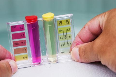Person measuring Ph level of spa