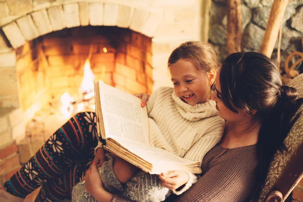 Mother reading book to daughter in front of a warm fireplace